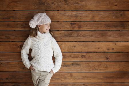 ni�o modelo: Linda ni�a de 9 a�os de edad que llevaba hecho punto oto�o o ropa de invierno posando sobre fondo de madera Foto de archivo