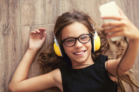 9 anni di età bambino è disteso sul pavimento, ascoltare musica e prendere selfie, punto vista dall'alto Archivio Fotografico - 44903650