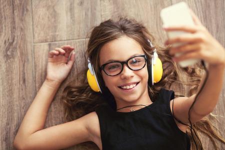 9 jaar oud kind is liggend op de vloer, luisteren naar muziek en het nemen van selfie, bovenaanzicht punt Stockfoto