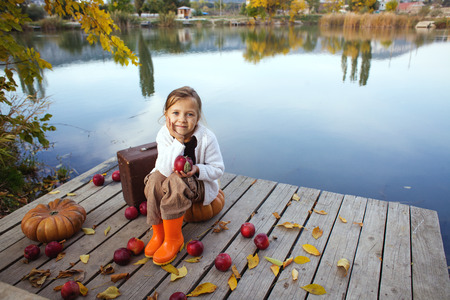 children pond: Cute little girl sitting on a vintage suitcase near the lake in warm autumn day. Halloween pumpkins, apples and fallen leaves beside.