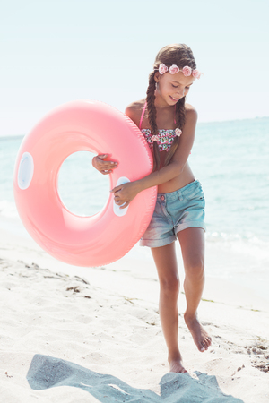 teen beach: 9 years old girl dressed in fashion floral swimsuit and denim shorts posing with inflatable ring at the beach in sunlight