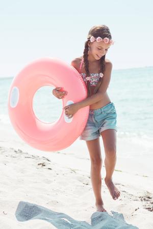 traje de bano: Niña de 9 años de edad vestido con la moda de trajes de baño floral y pantalones cortos de mezclilla posando con el anillo inflable en la playa en la luz del sol