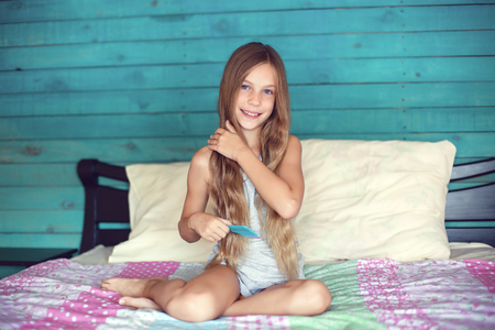 9 years old girl brushing her long hair in her bedroom in the morning