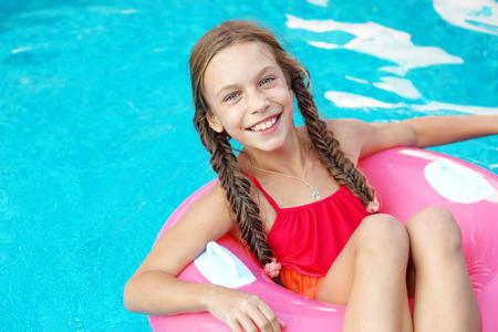 traje de bano: 9 años de edad niño jugando en la piscina en el anillo inflable