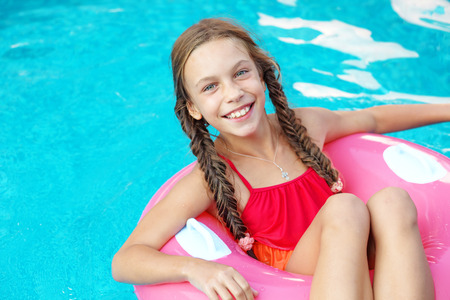 pool preteen: 9 years old child playing in the swimming pool on inflatable ring