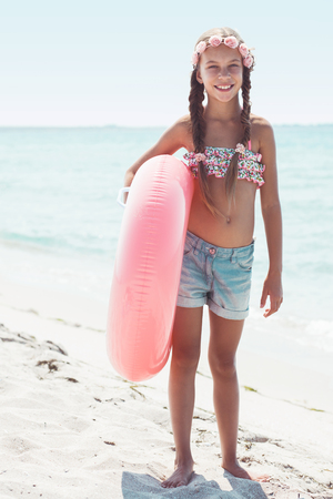 old girl: 9 years old girl dressed in fashion floral swimsuit and denim shorts posing with inflatable ring at the beach in sunlight