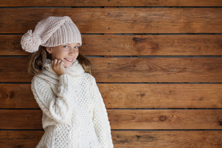 child model: Cute 9 years old girl wearing knitted autumn or winter clothing posing over wooden background Stock Photo