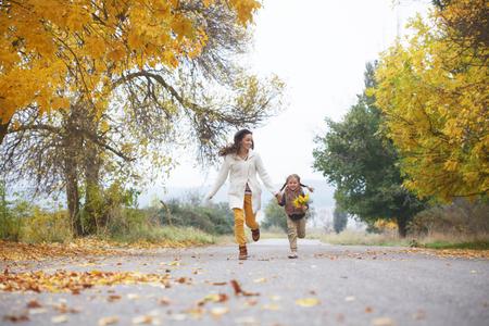otoñales: Joven madre con su pequeña hija que recorren en parque de la caída de las hojas amarillas caídas un día de otoño Foto de archivo