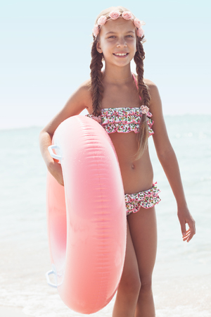 beach clothes: 9 years old girl dressed in fashion floral swimsuit posing with inflatable ring at the beach in sunlight Stock Photo