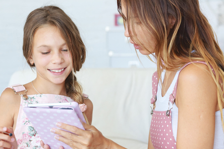preteen: Mother helps her preteen daughter learning together with tablet Stock Photo