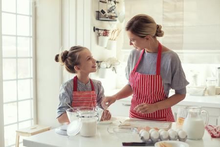 Mamá con sus 9 años de edad hija están cocinando en la cocina para el día de madres, la serie del estilo de vida foto en el interior casero brillante