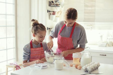 mama e hija: Mamá con sus 9 años de edad hija están cocinando en la cocina para el día de madres, la serie del estilo de vida foto en el interior casero brillante