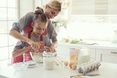 a kitchen: Mom with her 9 years old daughter are cooking in the kitchen to Mothers day, lifestyle photo series in bright home interior Stock Photo