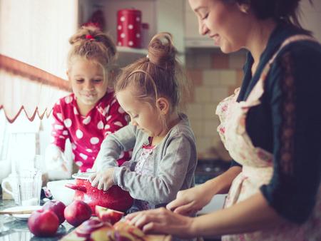 niños cocinando: Madre con sus 5 años de edad los niños de cocina pastel de fiesta en la cocina, estilo de vidas foto casual en el interior de la vida real