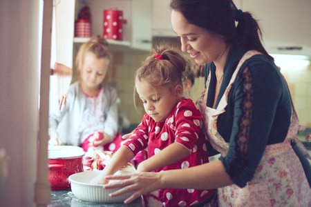 parent child: Mother with her 5 years old kids cooking holiday pie in the kitchen, casual lifestyle photo series in real life interior
