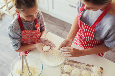mother cooking: Mom with her 9 years old daughter are cooking in the kitchen to Mothers day, lifestyle photo series in bright home interior Stock Photo