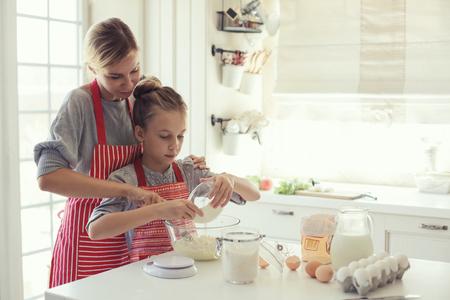 彼女の 9 歳の娘を持つお母さんが母の日にキッチン、明るいインテリア ライフ スタイル写真シリーズ料理します。