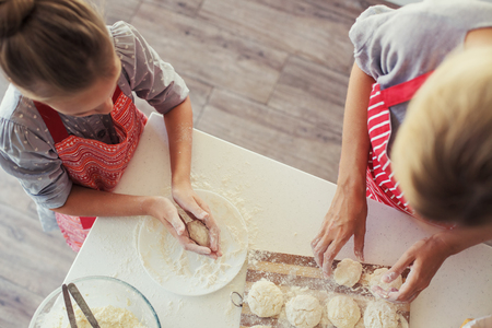 mother cooking: Mom with her 9 years old daughter are cooking in the kitchen to Mothers day, lifestyle photo series in bright home interior, top view point Stock Photo