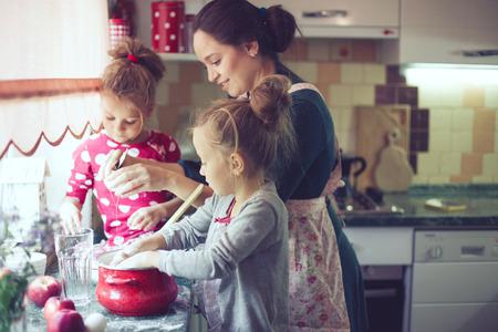 実際の生活インテリアでカジュアルなライフ スタイル写真シリーズ キッチンでホリデイ ・ パイを調理彼女の 5 歳の子供を持つ母