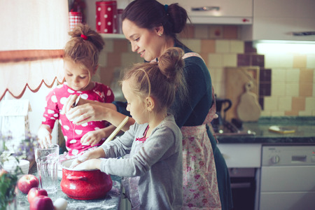 home cooking: Mother with her 5 years old kids cooking holiday pie in the kitchen, casual lifestyle photo series in real life interior