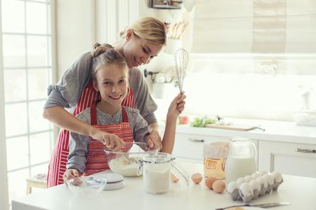 밝은 홈 인테리어에 그녀의 9 살 딸과 함께 엄마는 어머니의 날에 부엌에서 요리를, 라이프 스타일 사진 시리즈