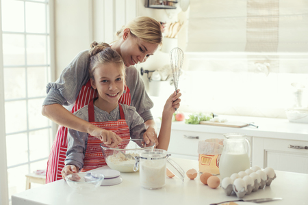 Mom with her 9 years old daughter are cooking in the kitchen to Mothers day, lifestyle photo series in bright home interior Stock Photo