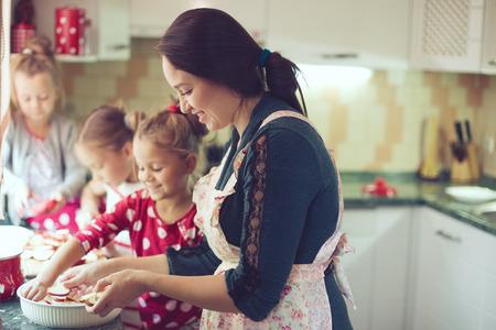 mujer hijos: Madre con tres niños de cocina pastel de vacaciones en la cocina, la serie del estilo de vida foto ocasional en el interior de la vida real