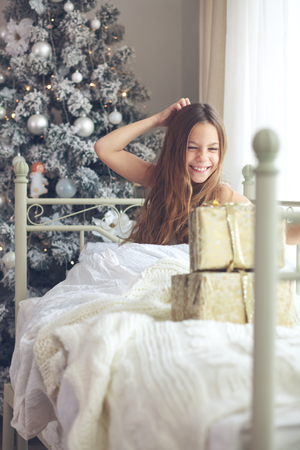 teenage girl happy: Preteen child girl wake up in her bed near decorated Christmas tree in beautiful hotel room in the holiday morning, enjoing with presents