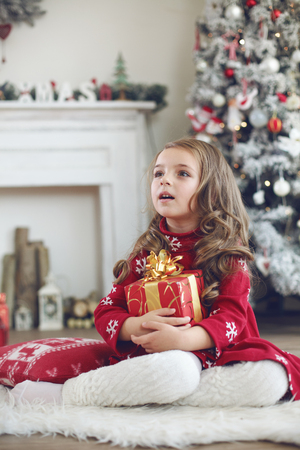 5 years: 5 years old little girl receives present from Santa Claus near Christmas tree in morning at home Stock Photo