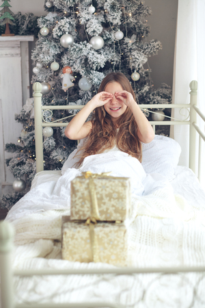 teen girl bedroom: Preteen child girl wake up in her bed near decorated Christmas tree in beautiful hotel room in the holiday morning, enjoing with presents