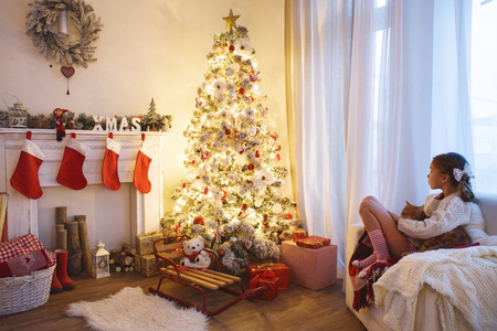 christmas morning: Child girl sitting near decorated Christmas tree and fireplace in comfortable chair at home Stock Photo