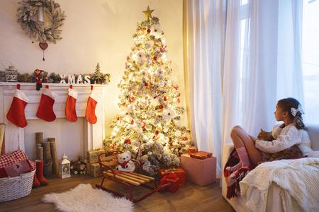 Menina da criança que senta-se perto da árvore de Natal decorada e lareira na cadeira confortável em casa Imagens