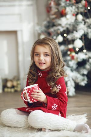 tomando leche: 5 años de edad niña leche de consumo cerca del árbol de Navidad en la mañana en su casa