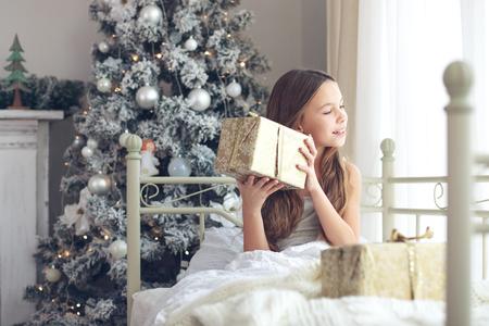 despertarse: Chica niño preadolescente despierta en su cama cerca del árbol de Navidad decorado en la hermosa habitación de hotel en la mañana de vacaciones, disfrutando con regalos