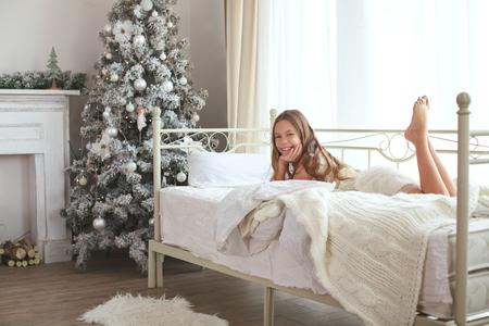 Preadolescente estela chica niño en su cama cerca del árbol de Navidad decorado en la hermosa habitación de hotel en la mañana de fiesta