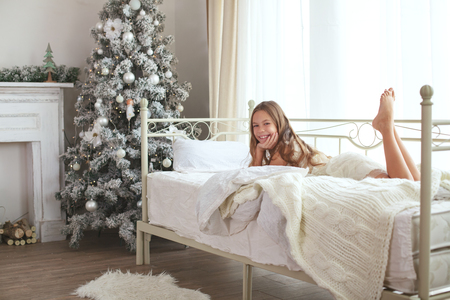 Preteen child girl wake up on her bed near decorated Christmas tree in beautiful hotel room in the holiday morning
