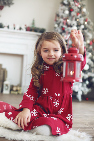 interior decor: 5 years old little girl drinking milk near Christmas tree in morning at home Stock Photo