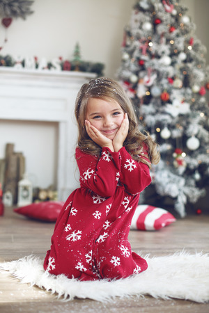 holiday house: 5 years old little girl posing near decorated Christmas tree at home