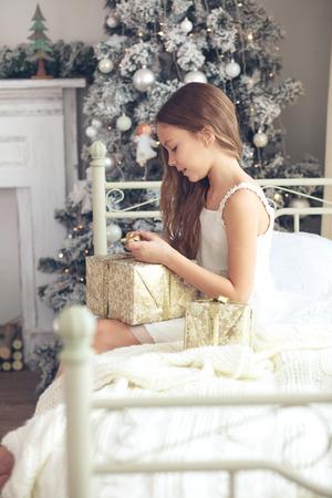 pijama: Preadolescente estela chica niño en su cama cerca del árbol de Navidad decorado en la hermosa habitación de hotel en la mañana de fiesta, que abren presentes