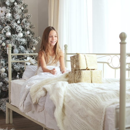 teenage girl happy: Preteen child girl wake up in her bed near decorated Christmas tree in beautiful hotel room in the holiday morning, surprised with presents Stock Photo