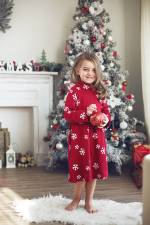 decorating christmas tree: 5 years old little girl decorating Christmas tree at home
