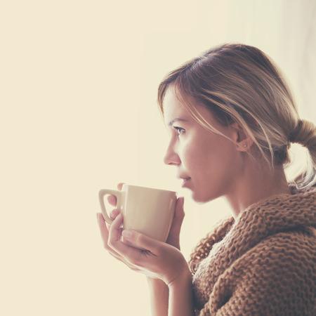 sueteres: Mujer que desgasta el su�ter hecho punto caliente est� bebiendo una taza de t� o caf� caliente cerca de la ventana en el oto�o de sol de la ma�ana, foto tonos c�lidos