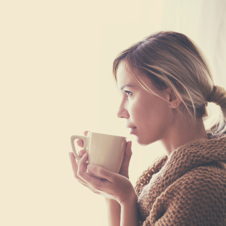 cold beverages: Woman wearing warm knitted sweater is drinking cup of hot tea or coffee near window in autumn morning sunlight, photo warm toned