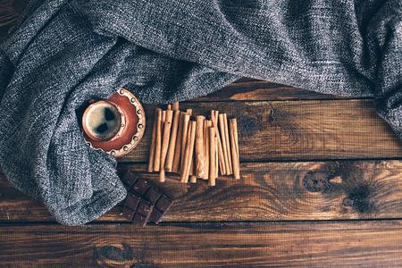 Pletení, káva a přikrývka na hnědé dřevěné podlaze, pohled shora bod