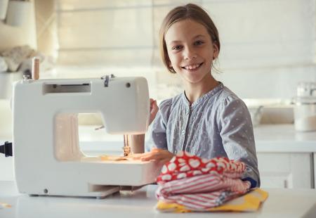 9 jaar oud kind studeren werken met de naaimachine Stockfoto