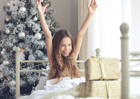 children santa claus: Preteen child girl wake up in her bed near decorated Christmas tree in beautiful hotel room in the holiday morning, enjoing with presents