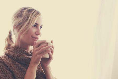 Žena na sobě teplý pletený svetr je pitná šálek horkého čaje nebo kávy u okna na podzim ranním slunci, fotografie teplých tónech