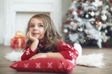 pijama: 5 años de edad niña que se establecen en el amortiguador suave y mirando hacia arriba cerca del árbol de Navidad en casa