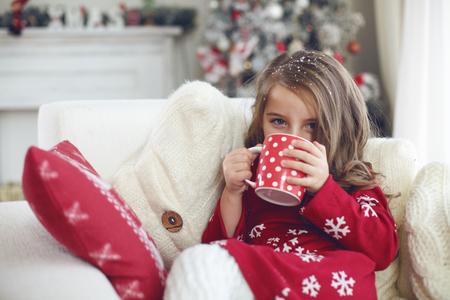 holiday house: 5 years old little girl sitting on cozy chair and drinking milk near Christmas tree in morning at home Stock Photo