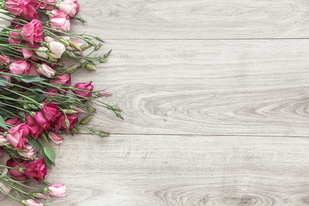 Pink eustoma flowers on natural wooden floor, selective focus, shabby chic style, space for custom text.